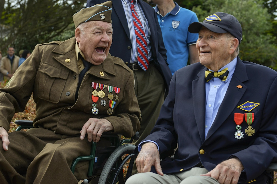 Two D-Day veterans who participated in the liberation of France share a laugh in Saint-Laurent-sur-Mer, France