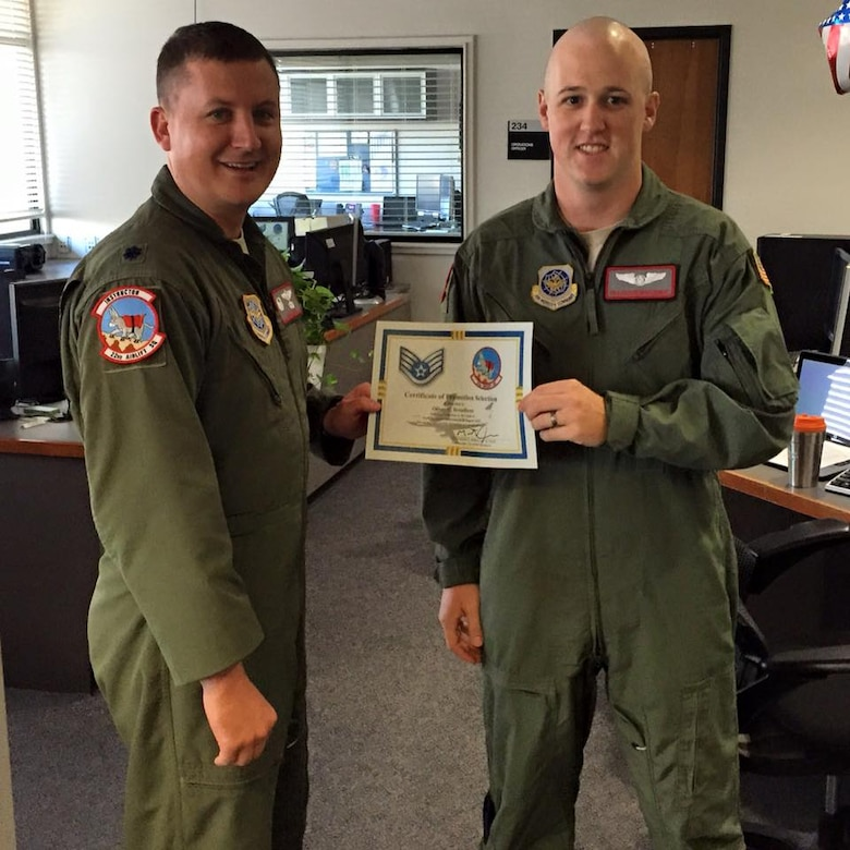 U.S. Air Force Lt. Col. Matthew Jones, the former 22nd Airlift Squadron commander, presents U.S. Air Force Staff Sgt. Oliver Broadbent, 22nd Airlift Squadron loadmaster, with a promotion certificate at Travis Air Force Base, Calif. (Courtesy photo)