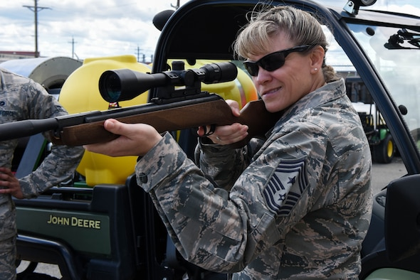Chief Master Sgt. Theresa Clapper, 2nd Bomb Wing command chief, shoots a pellet rifle while visiting the 2nd Civil Engineer Squadron Pest Management office, May 24, 2017. Pest management uses riffles to help control the wildlife populations of animals such as raccoons or opossums on base. (U.S. Air Force photo/Airman 1st Class Sydney Bennett)