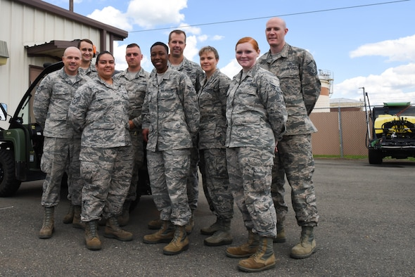 The 2nd Civil Engineer Squadron Pest Management office poses for a group photo with Col. Ty Neuman, 2nd Bomb Wing commander and Chief Master Sgt. Theresa Clapper, command chief, on Barksdale Air Force Base, La., May 24, 2017. Pest management catches feral dogs and wild hogs on base. (U.S. Air Force photo/Airman 1st Class Sydney Bennett)