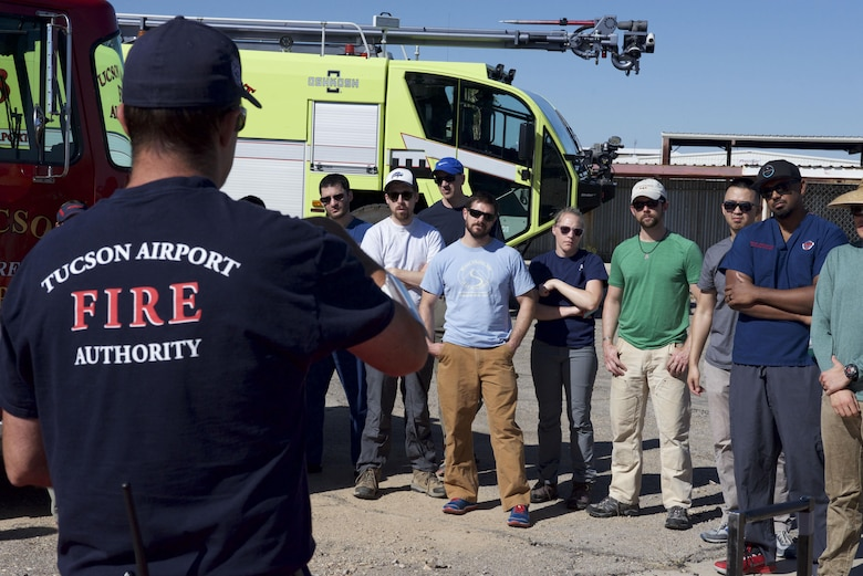 Levi Kring with the Tucson Airport Authority Fire Department gives residents from Banner University Medical Center a lesson  in automobile destruction during a patient extraction exercise at the airport, May 31.