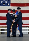 Maj. Gen. Christopher Bence, U.S. Air Force Expeditionary Center commander, left, passes the guidon to the new commander of the 319th Air Base Wing, Col. Benjamin Spencer, right, at an assumption of command ceremony June 6, 2017, on Grand Forks Air Force Base, N.D. Spencer is transitioning from Davis-Monthan Air Force Base, N.M., with his wife, Beth, and son, Evan. (U.S. Air Force photo by Airman 1st Class Elora McCutcheon)