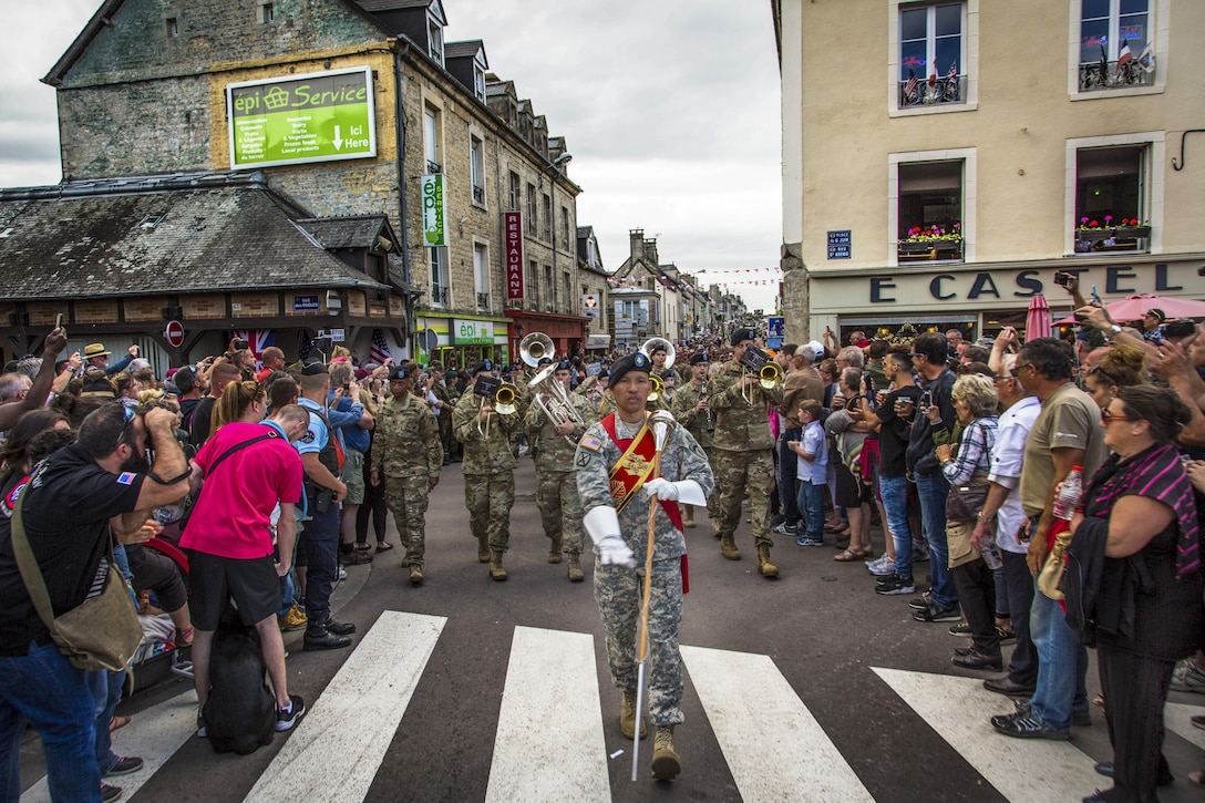 The U.S. Army Europe Band, led by drum major Staff Sgt. Redentor Aledia, marches in a parade in Sainte-Mere-Eglise, France