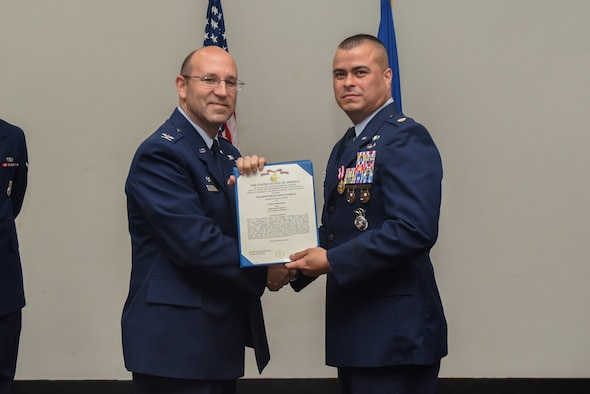 U.S. Air Force Col. Christopher Harris, 17th Mission Support Group Commander, presents a Meritorious Service certificate to Maj. Pedro Jimenez, 17th Security Forces Squadron commander, at the Event Center on Goodfellow Air Force Base, Texas, June 5, 2017. The event honored Jimenez' service and welcomed its new commander Maj. Min Lee. (U.S. Air Force photo by Airman 1st Class Chase Sousa/Released)