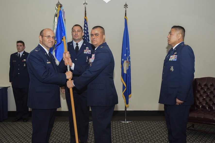 U.S. Air Force Maj. Pedro Jimenez, 17th Security Forces Squadron Commander, passes the unit guideon to Col. Christopher Harris, 17th Mission Support Group Commander, during the 17th SFS Change of Command ceremony at the Event Center on Goodfellow Air Force Base, Texas, June 5, 2017. The event honored Jimenez' service and welcomed its new commander Maj. Min Lee. (U.S. Air Force photo by Airman 1st Class Chase Sousa/Released)