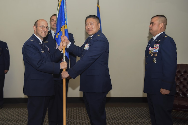 U.S. Air Force Maj. Min Lee, the new 17th Security Forces Squadron Commander, takes the guideon from Col. Christopher Harris, 17th Mission Support Group Commander, at the Event Center on Goodfellow Air Force Base, Texas, June 5, 2017. The event symbolizes the change of the 17 SFS commanders. (U.S. Air Force photo by Airman 1st Class Chase Sousa/Released)