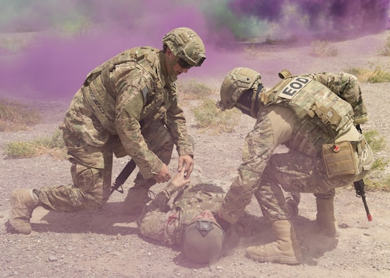 Explosive Ordnance Disposal Airmen check for life-signs on a simulated casualty during a Tactical Combat Casualty Care exercise at Holloman Air Force Base, N.M., on April 31, 2017. The training focuses on individual trauma, tools, techniques, and treatment procedures. The exercise also included the use of moulage, non-lethal training munitions, trained role-players, and a multitude of other artificial stressors. (U.S. Air Force Photo by Senior Airman Chase Cannon)