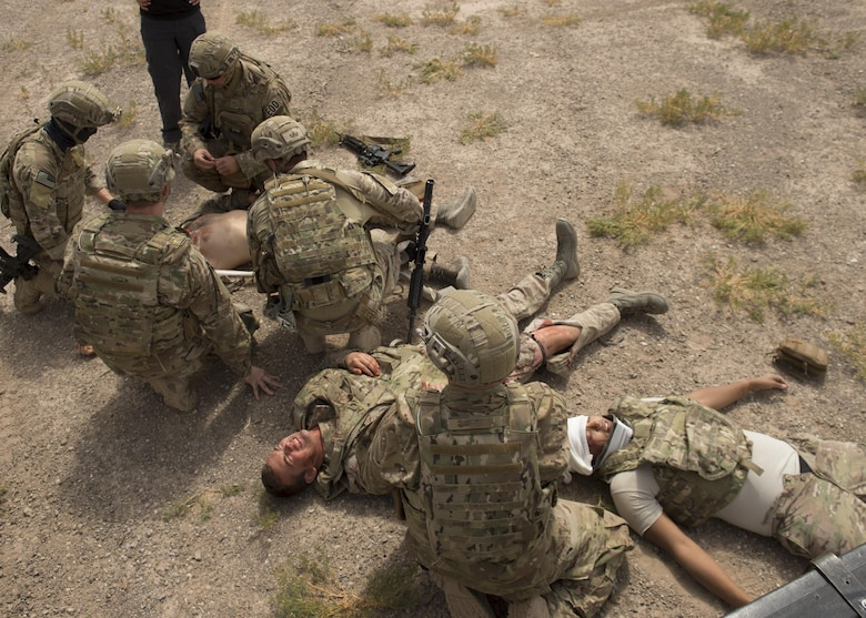Explosive Ordnance Disposal Airmen practice Tactical Combat Casualty Care techniques on a simulated casualty during an exercise at Holloman Air Force Base, N.M., on April 31, 2017. The training focuses on individual trauma, tools, techniques, and treatment procedures. The exercise also included the use of moulage, non-lethal training munitions, trained role-players, and a multitude of other artificial stressors. (U.S. Air Force Photo by Senior Airman Chase Cannon)