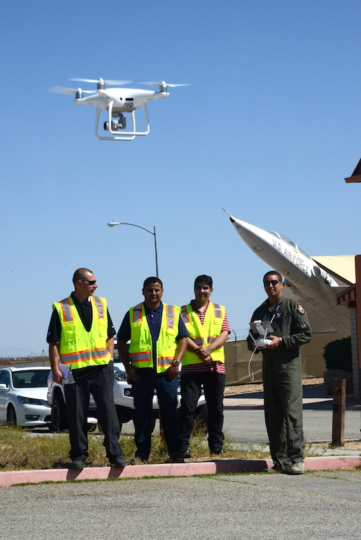 Maj. Danny Riley, director of the Emerging Technologies Combined Test Force, launches a small unmanned aerial system as members of the 412th Civil Engineer Group look on. The flight was done to evaluate its systems and to test its feasibility as a tool for the 412th Civil Engineer Group to perform roof inspections. (U.S. Air Force photo by Christopher Ball)