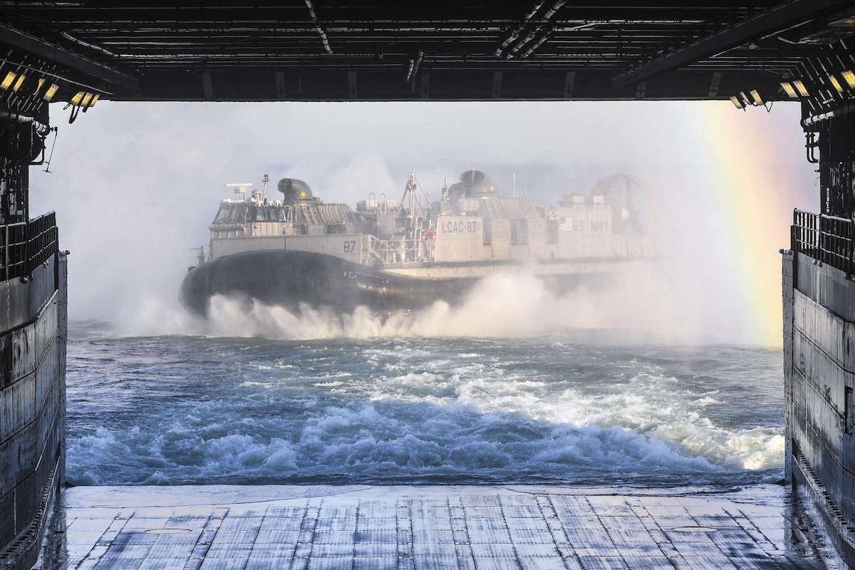 A Navy air-cushion landing craft departs the well deck of a ship.