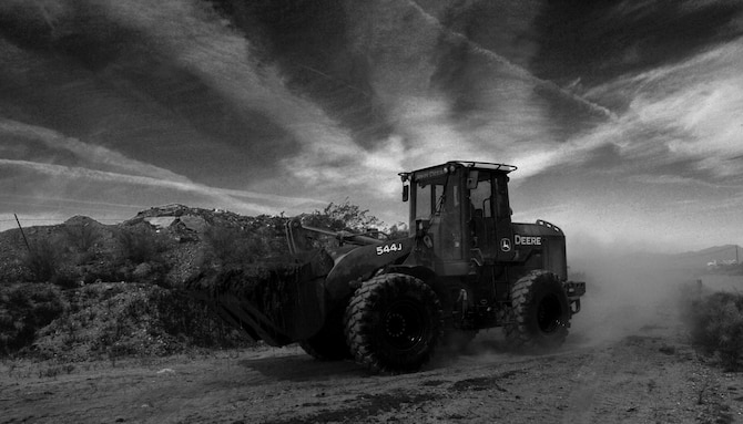 A loader carries a bucket full of sludge May 30, 2017 in Glendale, Az. Airmen from seven bases across the country partnered with Luke Air Force Base for the annual Bird/Wildlife Air Strike Hazard project to clear away more than 1000 tons of mud, vegetation and debris from around the perimeter of the base to deter the local bird and wildlife population and keep the airfields safe. (U.S. Air Force photo by Staff Sgt. Marcy Copeland)