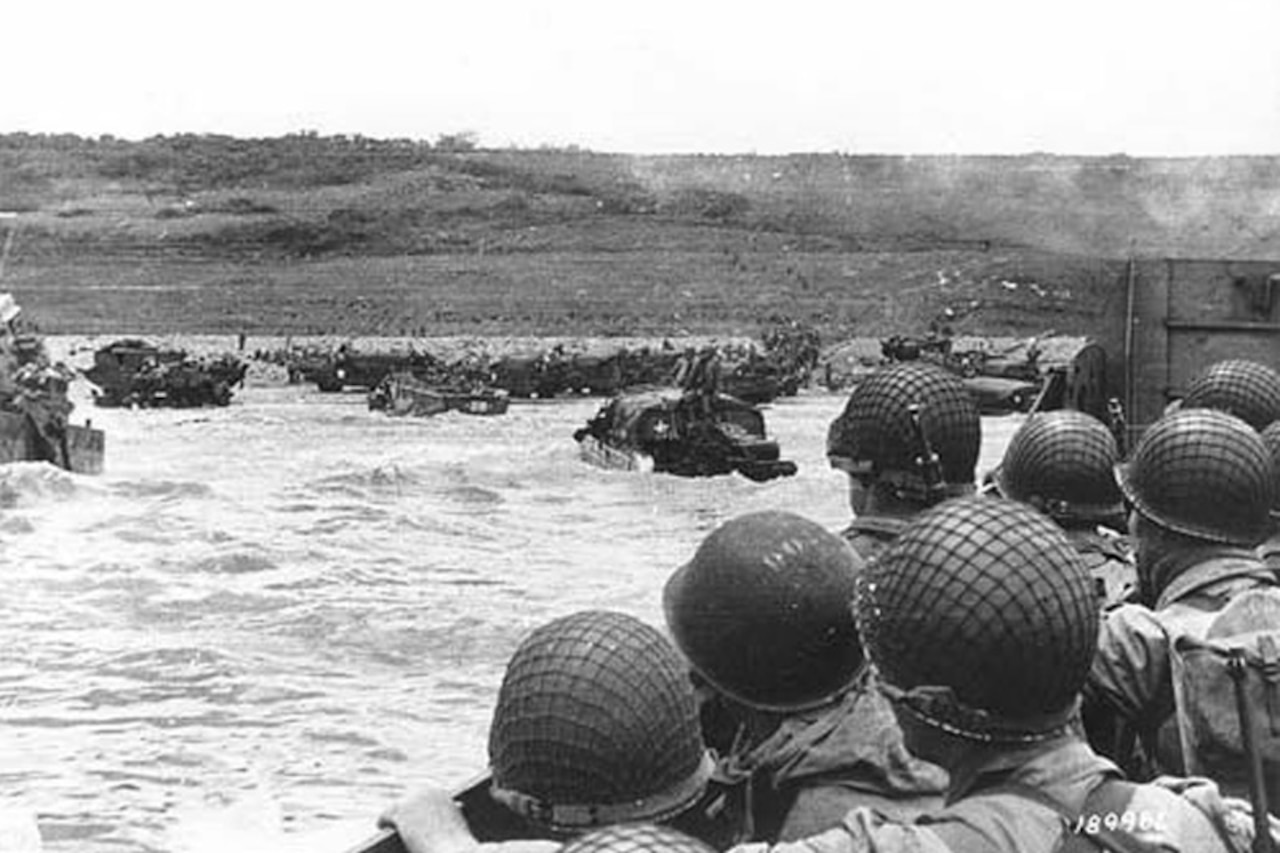 Soldiers in helmets look out at a beach from a landing craft.