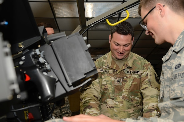 U.S. Army Staff Sgt. Adam Arafat, 128th Aviation Brigade instructor, shows U.S. Air Force Airman Tyler Barlow, 633rd Force Support Squadron force management apprentice, the inner-workings of a an AH-64 Apache helicopter during a tour at Joint Base Langley-Eustis, Va. June 2, 2017. The tour offered Airmen, assigned to the 633rd FSS, a chance to see what life is like as a 128th Avn. Bde. Advanced Individual Training student. (U.S. Air Force photo/Airman 1st Class Kaylee Dubois)
