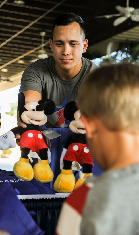 U.S. Air Force Staff Sgt. Christopher Stoltz, 647th Air Base Group photojournalist, hands out stuffed Mickey Mouses during the Books on Bases event at the Hickam Officers Club, hosted by Blue Star Families, Joint Base Pearl Harbor-Hickam, Hawaii, June 2, 2017.  Blue Star Families program donates books to military children, base libraries, Department of Defense schools, and military-impacted public schools and libraries across the world. (U.S. Air Force photo by Tech. Sgt. Heather Redman)