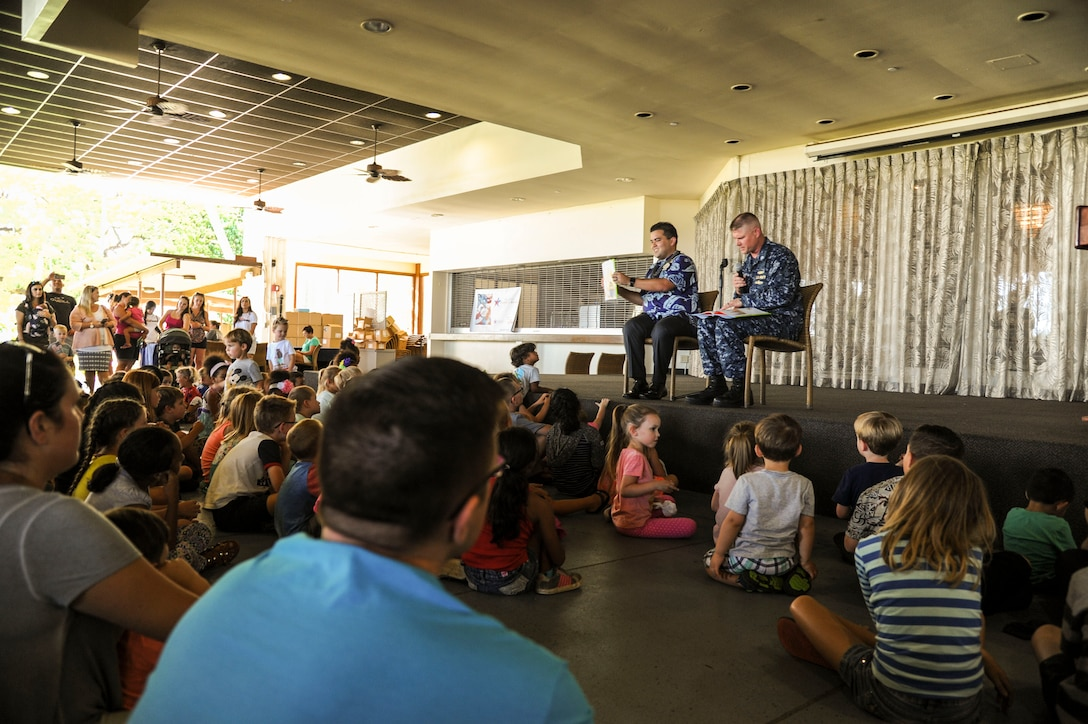 Manko Tamaka, Disney Resort ambassador, and U.S. Navy Commander Corey Hurd, Joint Base Pearl Harbor-Hickam chief staff officer, read Tommy Can't Stop by Tim Federle during the Books on Bases event at the Hickam Officers Club, hosted by Blue Star Families, Joint Base Pearl Harbor-Hickam, Hawaii, June 2, 2017.  Blue Star Families program donates books to military children, base libraries, Department of Defense schools, and military-impacted public schools and libraries across the world. (U.S. Air Force photo by Tech. Sgt. Heather Redman)
