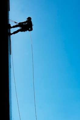 An Airman from the 5th Civil Engineer Squadron rappels down a building during an Expeditionary Training