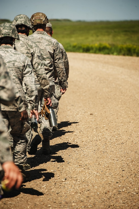 """Airman from the 5th Civil Engineer Squadron walk down a dirt road looking for simulated improvised explosive devices during an Expeditionary Training Day at Minot Air Force Base, N.D., June 1, 2017. The day consisted of a """"bag drag"""" and 6-mile ruck march, followed by tent set-up, rappelling, helicopter hoists, search-and-rescue training, convoy operations and Self-Aid and Buddy Care. (U.S. Air Force photo/Senior Airman J.T. Armstrong)"""