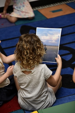 A pre-kindergarten student looks at a photograph of Air Force Staff Sgt. Miriam Y. Jarvis, 175th Force Support Squadron customer service NCO in charge, June 6, 2017, during a career day presentation at Oliver Beach Elementary School, Chase, Md. Jarvis was speaking to several classes about the Maryland Air National Guard and her role at the wing. (U.S. Air National Guard photo by Airman Sarah M. McClanahan /Released)