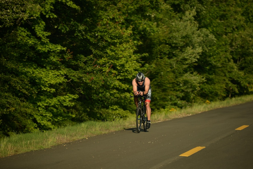 Maj. Alan Goncalves, 50th Flying Training Squadron Assistant Director of Operations, rides down Perimeter Rd. during a triathlon June 3, 2017, on Columbus Air Force Base, Mississippi. Goncalves finished the 22-kilometer bike ride in 35:24. He also finished overall in 1st with a time of 1:03:05. (U.S. Air Force photo by Airman 1st Class Keith Holcomb)