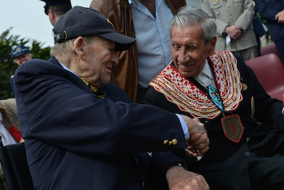 D-Day veterans George Kline and Charles Shay shake hands at the dedication ceremony for the Charles Shay Memorial in Saint-Laurent-sur-Mer, France