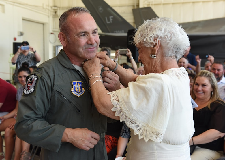 (Ret.) Col. Kurt Gallegos, 944th Fighter Wing former commander, stands while Elvia Gallegos, his mother, pins on his retirement pin June 3 during a retirement ceremony at Luke Air Force Base, Ariz. (U.S. Air Force photo by Staff Sgt. Lausanne Kinder)