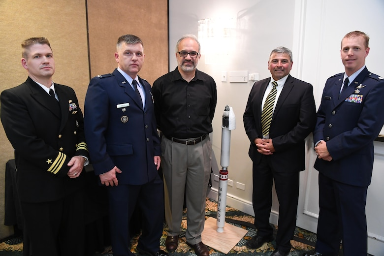 Representatives of the Joint Functional Component Command for Space, 14th Air Force (Air Forces Strategic) and Operationally Responsive Space office from Vandenberg Air Force Base, California, pose for a group photo with California Polytechnic University staff during a satellite design conference hosted by Cal Poly in Shell Beach, California, June 2, 2017.  The conference focused on the presentation of the aerospace engineering student capstone project to assembled military and industry space experts. (U.S. Air Force photo by Capt. Nicholas Mercurio/Released)