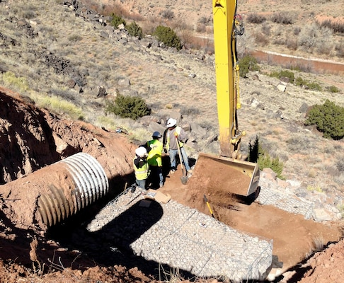 JEMEZ DAM, N.M. – Due to concerns that moving equipment into the area downslope of the culvert might damage cultural resources, the BLM crew used long-reach equipment from above to repair the culvert, Mar. 2, 2017.
