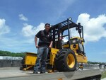 A member of the Guam Police Department prepares to transport the former military forklift his department received for use lifting barriers and placing damaged patrol cars on trailers for transport to the repair facility.
