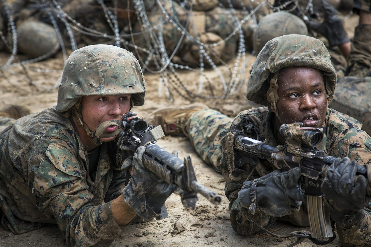 Marine Corps recruits aim weapons as they post security during basic training.