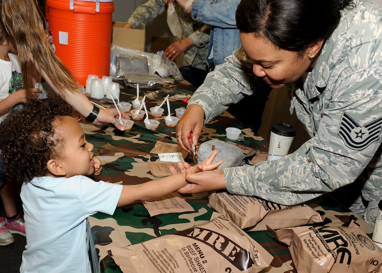 A child receives candy after sampling a Meal Ready-to-Eat during Operation Heroes at Minot Air Force Base, N.D., June 3, 2017. During the event, children tasted Meals Ready-to-Eat, tried on gear, saw weapons displays and created custom-made dog tags. The event concluded with a redeployment line and a welcome home celebration. (U.S. Air Force photo/Senior Airman Sahara L. Fales)