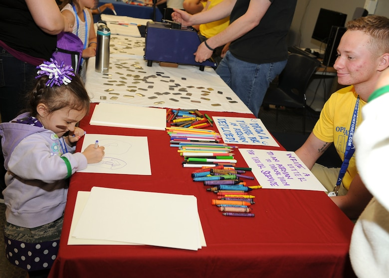 A child colors a picture during Operation Heroes at Minot Air Force Base, N.D., June 3, 2017. During the event, children tasted Meals Ready-to-Eat, tried on gear, saw weapons displays and created custom-made dog tags. The event concluded with a redeployment line and a welcome home celebration. (U.S. Air Force photo/Senior Airman Sahara L. Fales)