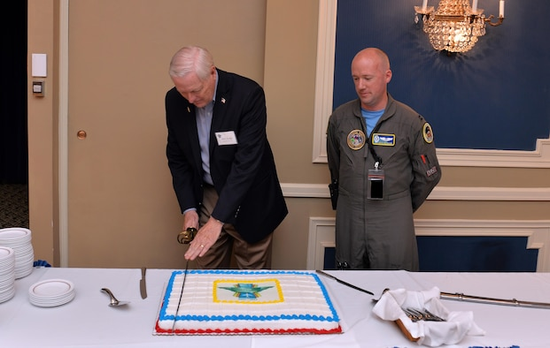 Retired Maj. Gen. Robert Parker, the first commander to lead the Airborne Launch Control System in 1967, ceremoniously cuts the anniversary cake with a saber alongside Capt. Paul Bouvier, a missileer assigned to the 625th Strategic Operations Squadron, at the 50th Anniversary celebration held June 2. the Patriot Club, Offutt Air Force Base, Neb. Over 80 Airmen both active duty and retired attended the event to celebrate the 50th anniversary of the Airborne Launch Control System. (U.S. Air Force photo by Josh Plueger)