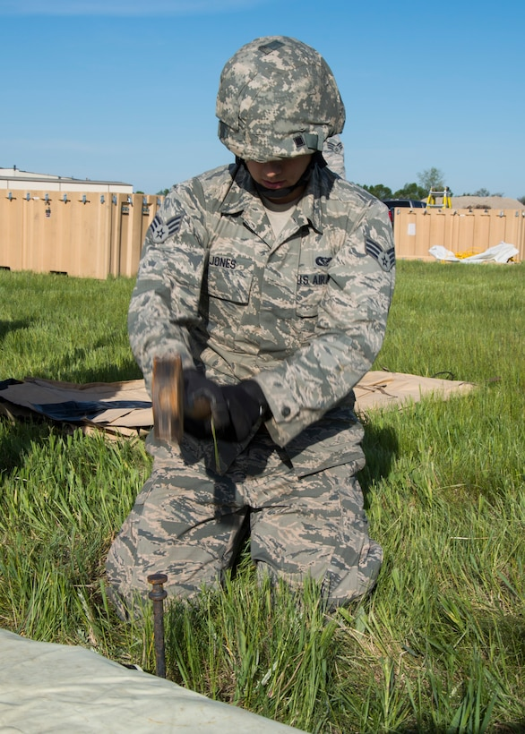 Senior Airman John Jones, 5th Civil Engineer Squadron structural apprentice, hammers a stake into the ground at Minot Air Force Base, N.D., June 1, 2017. The 5th CES built two tents during Expeditionary Training Day to help Airmen prepare for potential deployment. (U.S. Air Force photo/Airman 1st Class Alyssa M. Akers)