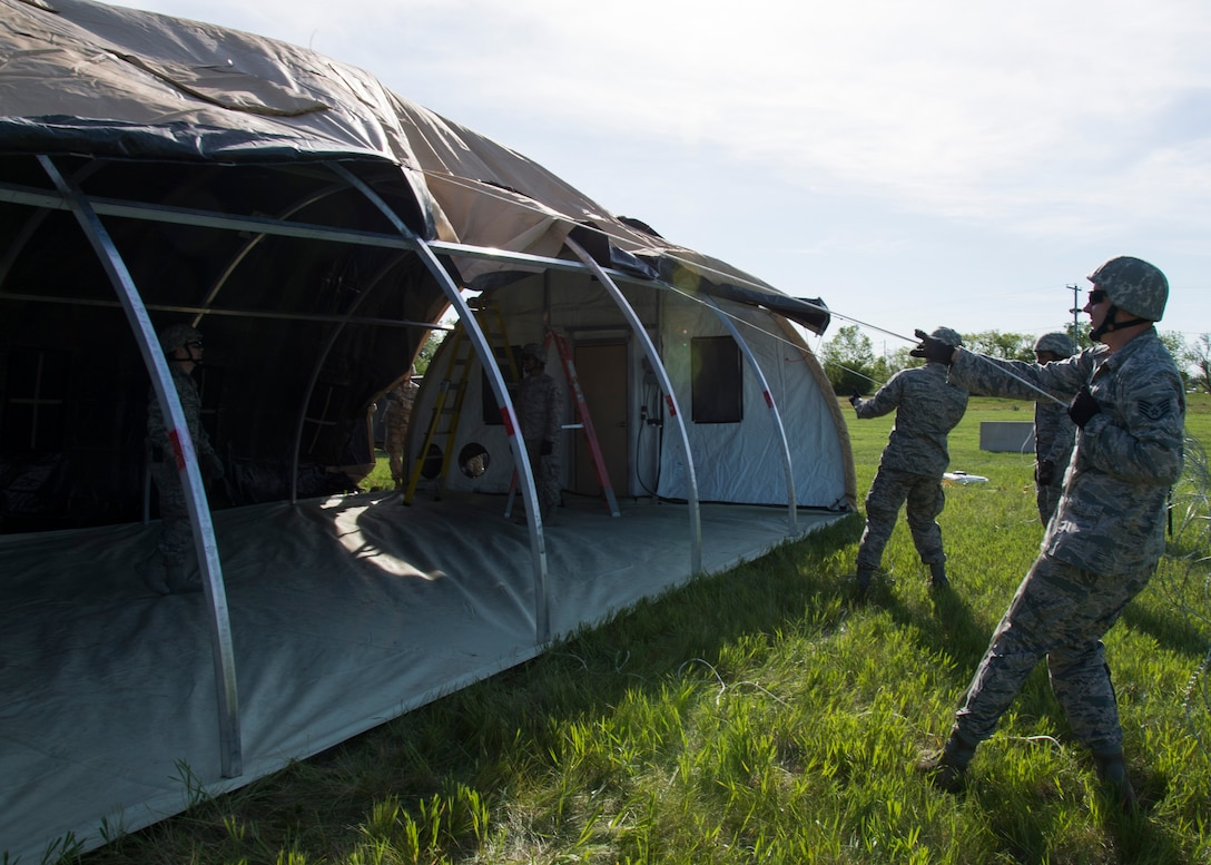 Airmen from the 5th Civil Engineer Squadron build a tent at Minot Air Force Base, N.D., June 1, 2017. The 5th CES built two tents during Expeditionary Training Day, an event that prepares Airmen for potential deployment. (U.S. Air Force photo/Airman 1st Class Alyssa M. Akers)