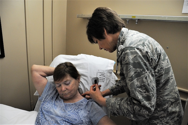 "Lt. Col Candy Wilson (right), 779th Medical Group nurse practitioner, places a Nerve Scrambler electrode inches away from the source of nerve pain on the back of a patient's neck May 30, 2017 at Joint Base Andrews, Md. Another electrode will be placed on the patient's foot where she feels no pain. The low electrical current that passes through the electrodes to Grays body causes a ""no pain"" signal to override the existing pain signal being sent to the patient's brain. (U.S. Air Force photo by Staff Sgt. Joe Yanik)"