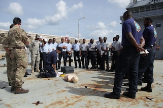 Sapper Lee McAulay of the British Army guides members of the Trinidad & Tobago Coast Guard through a simulated first aid scenario during first aid training at Exercise Tradewinds 2017 in Bridgetown, Barbados, June 7, 2017.  Tradewinds 2017 is a joint, combined exercise conducted in conjunction with partner nations to enhance the collective abilities of defense forces and constabularies to counter transnational organized crime, and to conduct humanitarian/disaster relief operations. (Royal Bahamas Defense Force photo by Marine Seaman Michael Turner/Released)