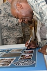 Chief Master Sgt. of the Air Force Kaleth O. Wright signs a picture while visiting the 51st Dental Squadron at Osan Air Base, Republic of Korea, June 7, 2017. Wright is a prior dental technician stationed at Osan and signed the photo to add to the Dental Clinic's Hall of Fame. (U.S. Air Force photo by Airman 1st Class Gwendalyn Smith/Released)