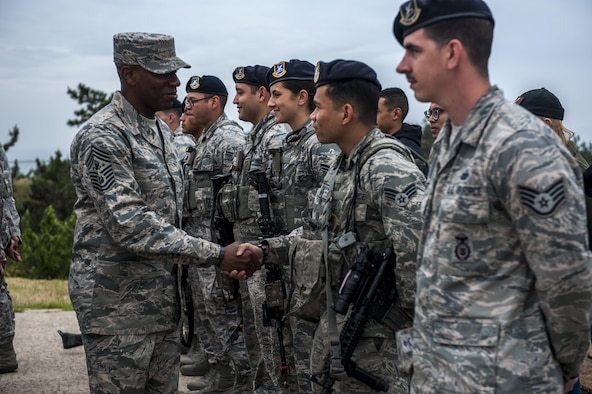 "Chief Master Sgt. of the Air Force Kaleth O. Wright shakes hands with an Airman assigned to the 8th Security Forces Squadron as he takes a tour of the squadrons at Kunsan Air Base, Republic of Korea, June 6, 2017. 8th SFS showcased their role in the first priority of Wolf Pack's mission to, ""Defend the Base."" (U.S. Air Force photo by Senior Airman Colville McFee/Released)"