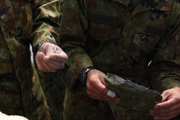 Members of the Japan Ground Self-defense Force interact with a glove and powder used by the 1-1 Air Defense Artillery battalion during chemical, biological, radiological and nuclear defense decontamination exercises, May 18, 2017, at Kadena Air Base, Japan. 1-1 ADA members hosted JGSDF and members of the 18th Wing, demonstrating CBRN decontamination practices on the Patriot missile system. (U.S. Air Force photo by Senior Airman Nick Emerick)