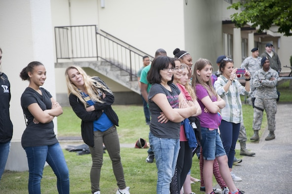 Youth from the Misawa Teen Center watch as U.S. Air Force Staff Sgt. Charles Sena, a 35th Security Forces Squadron military working dog handler, demonstrates MWD Karo's skills at Misawa Air Base, Japan, June 7, 2017. The focus of the event was to teach teens about weapons 35th SFS members' use, the MWD section and what they do on a day-to-day basis. (U.S. Air Force photo by Staff Sgt. Melanie A. Hutto)