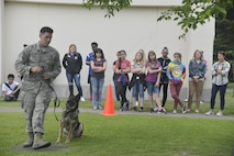 U.S. Air Force Staff Sgt. Charles Sena, a 35th Security Forces Squadron military working dog handler, demonstrates MWD Karo's discipline with a variety of commands during a security forces immersion with kids from the teen and youth centers at Misawa Air Base, Japan, June 8, 2017. The event is part of a project by the Boys and Girls Club curriculum for the Misawa Teen Center implements into the different clubs they offer. The focus helped establish a relationship between teens and security forces. (U.S. Air Force photo by Capt. Samantha Morrison)