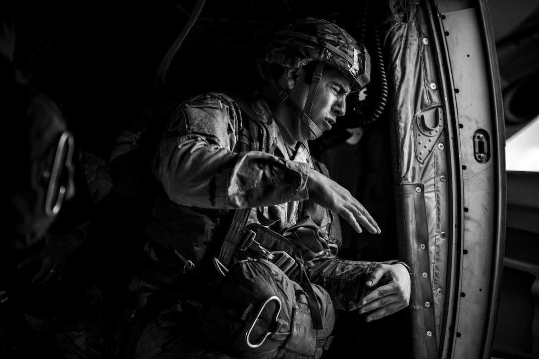 A U.S. Army soldier braces against the wind from the open side door of a U.S. Air Force C-130J Super Hercules assigned to the 37th Airlift Squadron at Ramstein Air Base, Germany, before jumping out near Sainte-Mere-Eglise, France, June 4, 2017. This event commemorates the 73rd anniversary of D-Day, the largest multinational amphibious landing and operational military airdrop in history, and highlights the U.S.' steadfast commitment to European allies and partners. Overall, approximately 400 U.S. service members from units in Europe and the U.S. are participating in ceremonial D-Day 73 events from May 31-June 7, 2017. (U.S. Air Force photo by Senior Airman Devin Boyer)