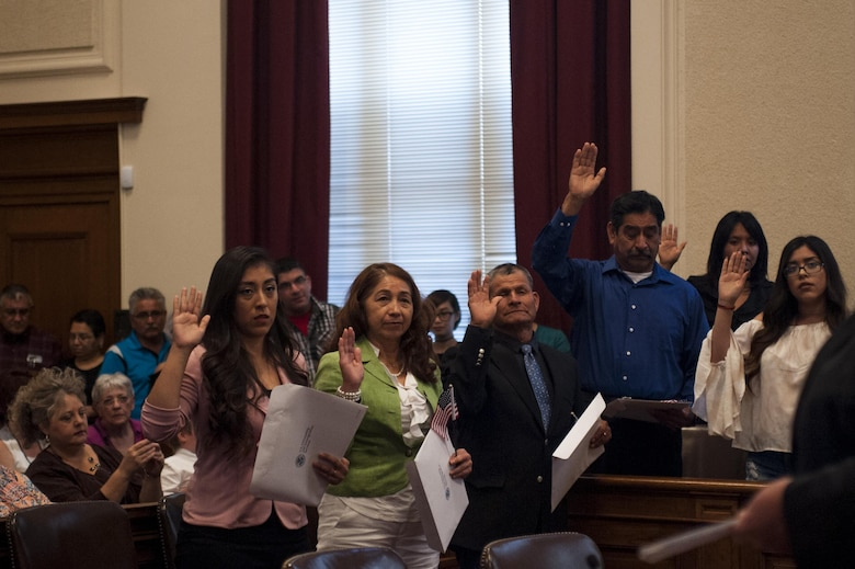 Newly nationalized American citizens swear an oath of citizenship in the O.C. Fisher Building, San Angelo, Texas, June 7, 2017. The naturalization ceremony gave citizenship to individuals from almost every part of the world including Mexico, China, Malaysia, Brazil and Nicaragua. (U.S. Air Force photo by Senior Airman Scott Jackson/Released)