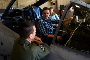 Thomas Johnson, an operations research analyst with the Cost Analysis and Program Evaluation office, sits in the pilot's seat of an A-10 Thunderbolt II aircraft while talking about the aircraft's capabilities with Air Force Lt. Col. Rich Hunt, left, a pilot with the Maryland Air National Guard's 104th Fighter Squadron, as other members of CAPE look on during a visit to Warfield Air National Guard Base, Maryland, June 1, 2017.