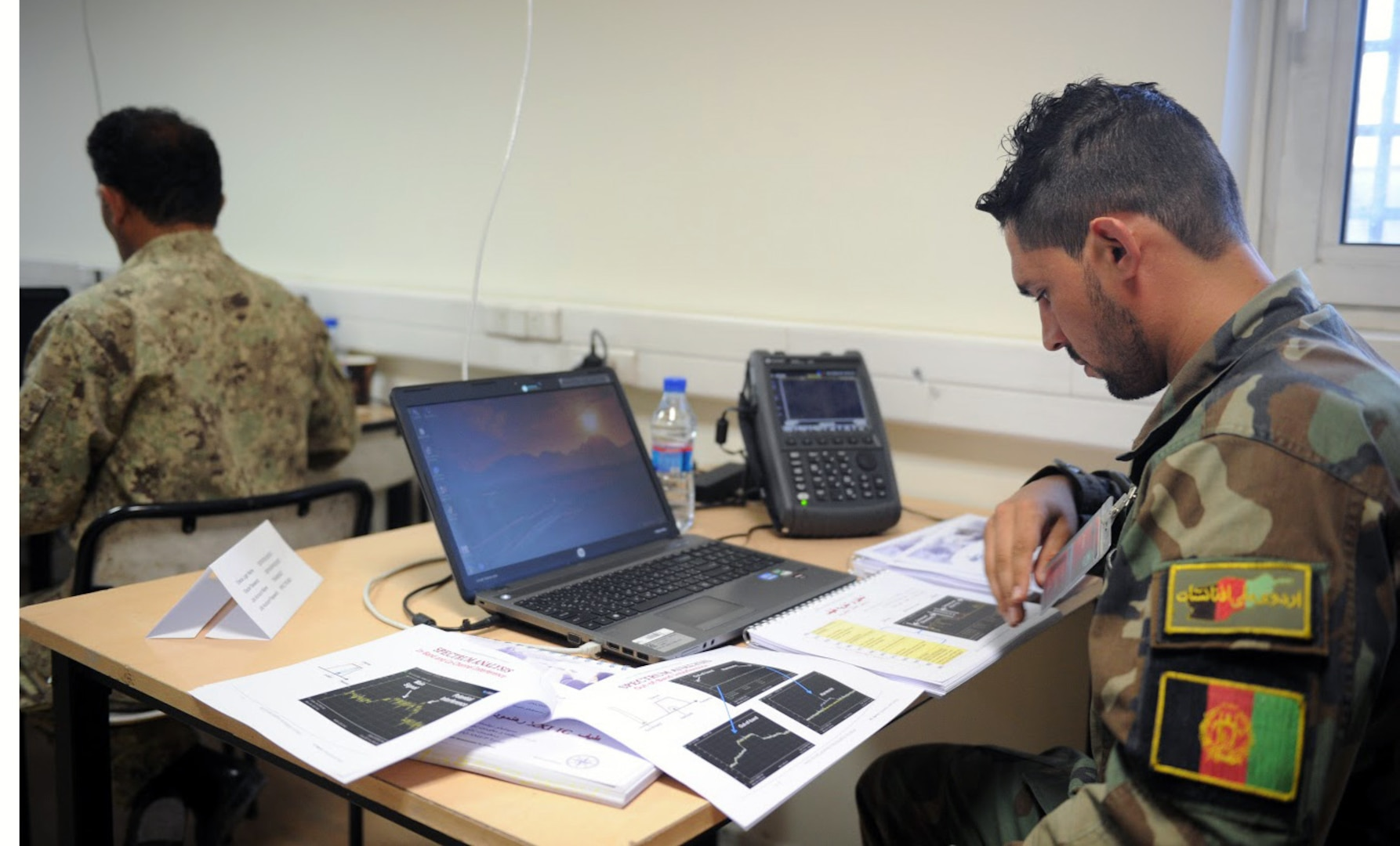KABUL, Afghanistan (June 7, 2017) —1st Lt. Ahmad Shoaib Nabizada, honorary graduate, looks at his notes during the Spectrum Management class. The Afghan National Defense and Security Forces are to integrate its newest graduates in communication operations. These soldiers will be responsible for generating and ensuring accurate radio frequency signals, essential for combat operations, rescue missions and logistic support. (U.S. Navy photo by Lt. j.g. Egdanis Torres Sierra, Resolute Support Public Affairs – Afghanistan)