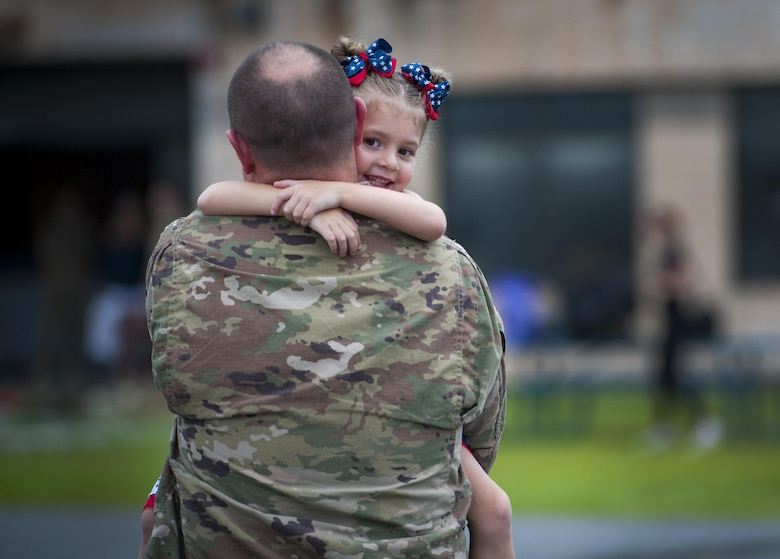 Staff Sgt. Matthew Pearson, 71st Aircraft Maintenance Unit navigation specialist, holds his daughter, Savannah, during a redeployment, June 6, 2017, at Moody Air Force Base, Ga. The 41st and 71st Rescue Squadrons were recently deployed to Southwest Asia where they provided combat search and rescue capabilities in support of Operation Inherent Resolve. (U.S. Air Force photo by Airman 1st Class Lauren M. Sprunk)