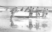 Nauset Life-Saving crew launching their surfboat, all wearing mixed uniforms with wading boots and cork life vests; no date, possibly post-1915 era.