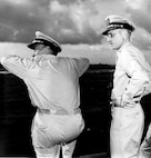 Officers: standard Navy-issue tropical khakis; Coast Guard devices on shoulder boards & hats.