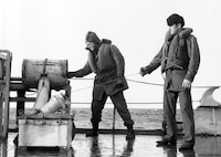 """Winter clothing, kapok life vests.  Coast Guardsman on right is wearing the standard Navy issue watch cap.    They are preparing to fire a """"K"""" gun depth charge projector."""