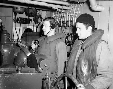 Helmsman and talker on the bridge of a cutter at sea in the North Atlantic, WWII